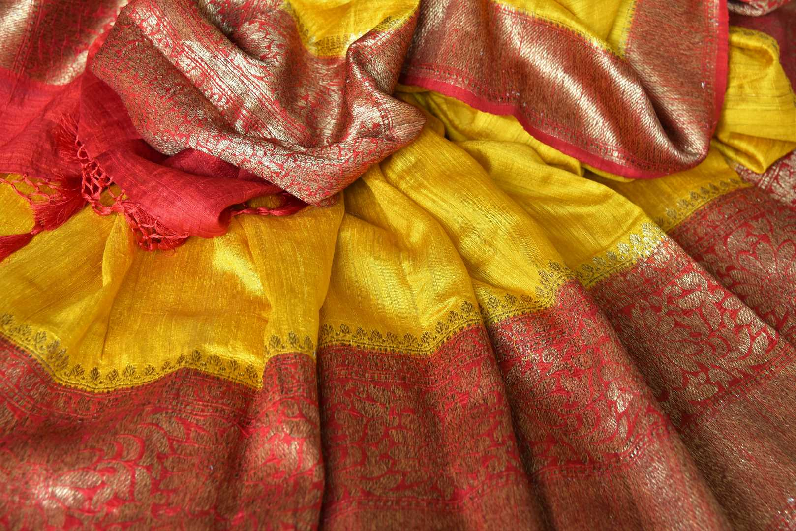 Exude a flair of elegance in this scintillating bright yellow matka banarsi silk saree. It comes with a gorgeous red zari border and complemented well with a contrasting red zari designer blouse. Shop handcrafted silk sarees, linen sari, georgette saree online or visit Pure Elegance store, USA.-details