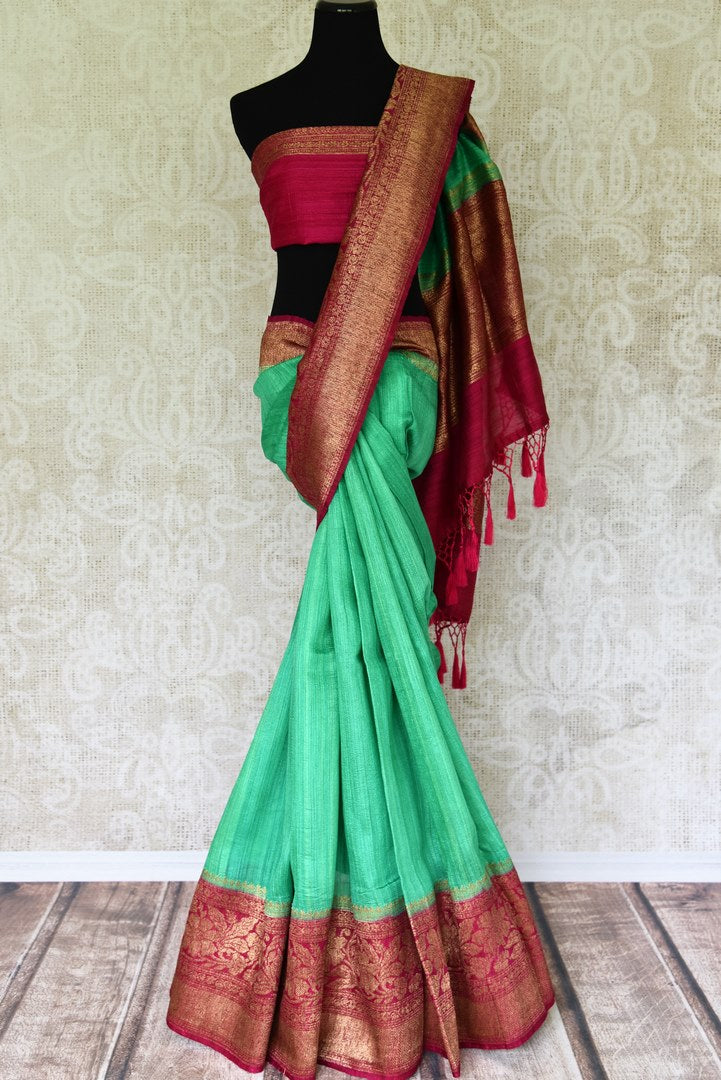 Leave them enthralled as you step up your style game in this mint green matka banarsi silk saree with a stunning red zari border. Elevate your look with a contrasting red zari designer blouse and heavily woven pallu. Shop designer silk sarees, embroidered sari, kalamkari sari online or visit Pure Elegance store, USA.-full view