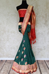 Drape the authentic weaves of green banarsi silk saree with intricately woven floral buta work. The gorgeous blend of red woven pallu adds elegance. Style this sari with a contrast red buta work designer blouse. Shop such designer silk sari, linen saree, chiffon sari online or visit Pure Elegance store, USA. -full view