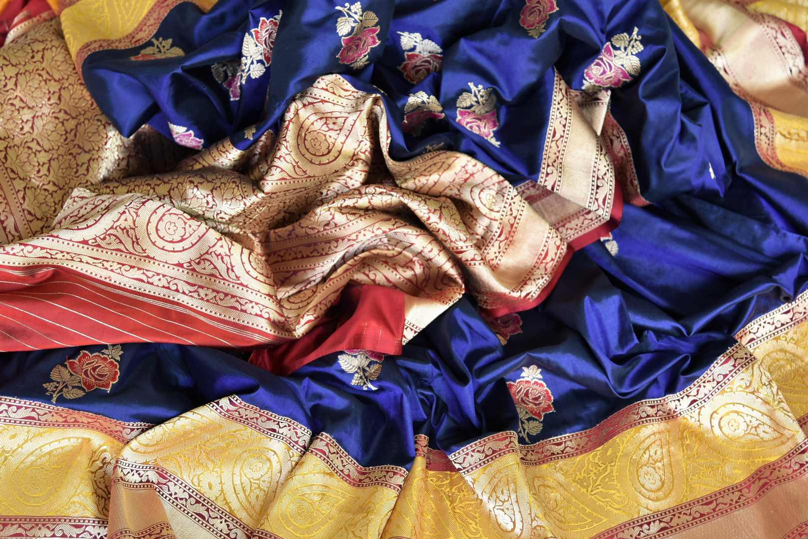 Exude elegance in our royal blue banarsi silk authentic sare. The subtle contrast of cream zari border complemented with the deep rich red buta work blouse is indeed a spectacular sight. Style this to weddings and parties. Shop designer silk sari, chiffon saree, linen sari online or visit Pure Elegance Store, USA. -details