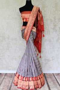Strut in style in this grey banarsi silk saree with a stunning red zari border. It features an exquisite check pattern and glorious shine on the drape. Style this gorgeous sari with a contrast red zari detailed blouse. Shop kanjeevaram silk sari, georgette saree, chiffon sari online or visit Pure Elegance store, USA.-full view