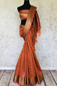 Exude sheer elegance in this gorgeous brown matka banarsi silk saree. It comes with a stunning zari weave border gracing the sari. Style it with a statement zari gold weave blouse to ooze the oomph. Shop handcrafted designer silk saris, printed saree, embroidery sari online or visit Pure Elegance store, USA.-full view