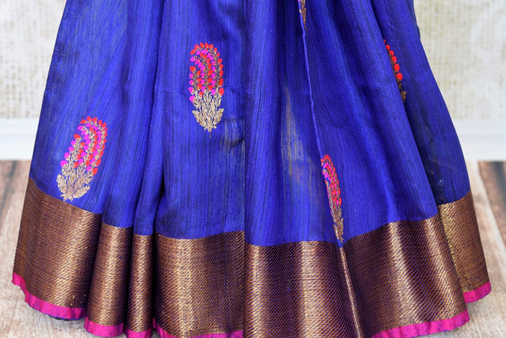Indulge in this scintillating royal blue matka banarsi silk saree. It comes with a gorgeous zari weave border and contrasting blue zari blouse to create a stunning ensemble. The intricately woven butas all over the sari looks beautiful. Shop designer silk sari, printed saree online or visit Pure Elegance store, USA.-pleats
