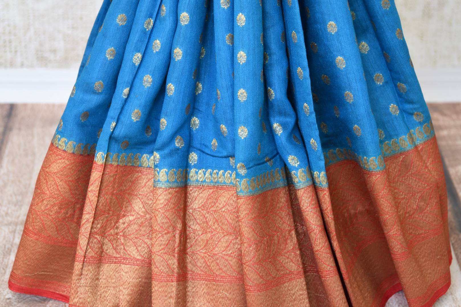 Buy blue tussar Benarasi saree online in USA with red zari border and zari buta. Make an elegant ethnic fashion statement at parties, weddings and special occasions with a splendid collection of Indian designer sarees, Benarasi saris, wedding sarees from Pure Elegance Indian clothing store in USA or shop online.-pleats
