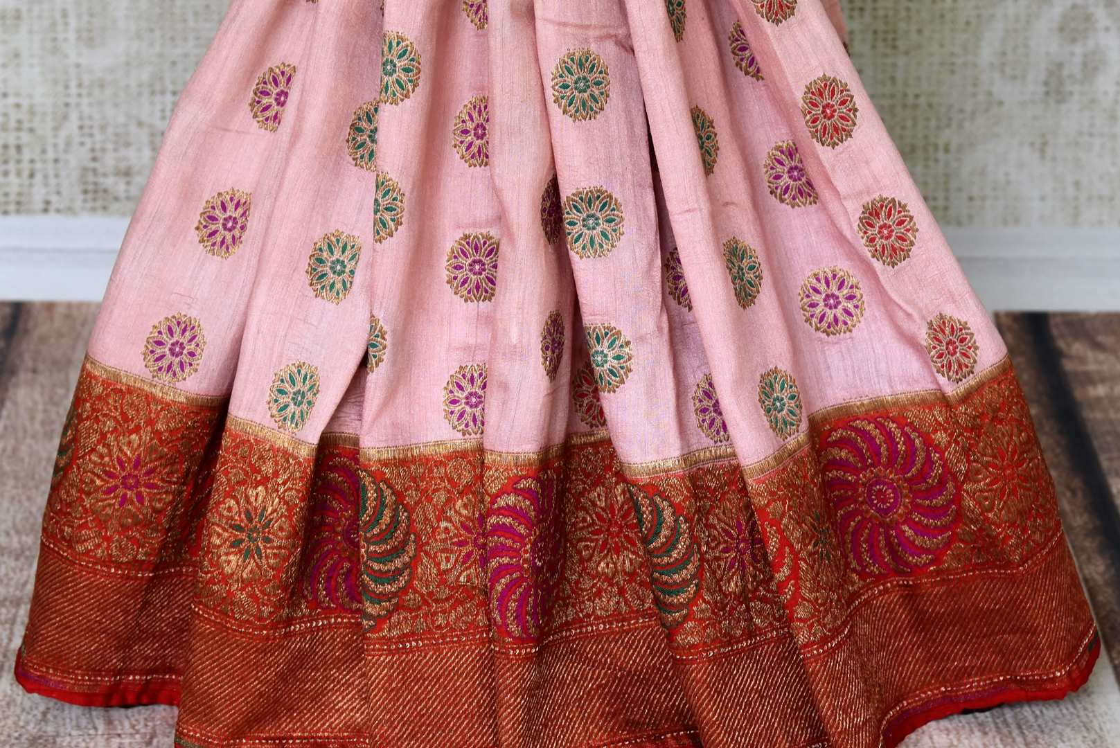 Grace with finesse in this gorgeous pink muga banarsi silk saree. Woven with pretty motifs all-over, it features a rich red zari border and complemented well with a contrasting red zari blouse to enrich the ensemble. Shop designer silk sarees, georgette sari, organza sari online or visit Pure Elegance store, USA.-pleats