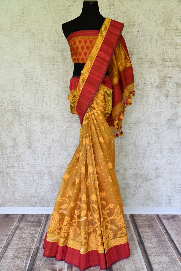 Feel like a diva in this modern fusion orange kora organza saree. This designer sari features elaborate design all-over complemented with a stunning red border. Style it with a designer orange and red buta work blouse. Shop handloom sarees, banarsi silk sari, georgette saree online or visit Pure Elegance store, USA. -full view