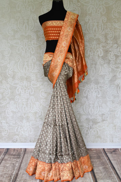 Strut like a diva in this designer grey banarsi silk saree. It comes with a peach zari border that enhances the beauty of this silk sari. You can add a spin to this stylish ensemble with a designer peach buta work blouse. Shop handcrafted silk saree, linen sari, chiffon saree online or visit Pure Elegance store, USA. -full view