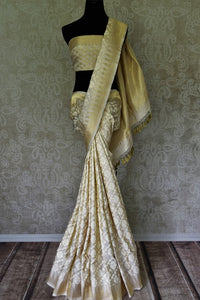 Off-white Benarasi silk saree with temple zari border buy online in USA and floral design. Adorn your style with a range of exquisite handloom sarees from Pure Elegance Indian clothing store in USA. We have an exquisite range of Indian designer sarees, silk sarees, Banarasi saris and many other varieties also available at our online store.-full view