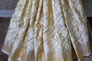 Off-white Benarasi silk saree with temple zari border buy online in USA and floral design. Adorn your style with a range of exquisite handloom sarees from Pure Elegance Indian clothing store in USA. We have an exquisite range of Indian designer sarees, silk sarees, Banarasi saris and many other varieties also available at our online store.-pleats