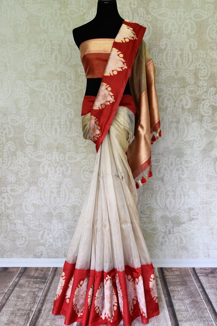 Buy white Banarasi silk saree online in USA with red border with big zari buta. Find an exquisite range of Banarasi sarees in USA at Pure Elegance Indian clothing store. Enhance your ethnic look with a variety of silk sarees, Kanchipuram sarees, and Indian jewelry available at our online store.-full view