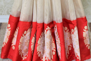 Buy white Banarasi silk saree online in USA with red border with big zari buta. Find an exquisite range of Banarasi sarees in USA at Pure Elegance Indian clothing store. Enhance your ethnic look with a variety of silk sarees, Kanchipuram sarees, and Indian jewelry available at our online store.-pleats