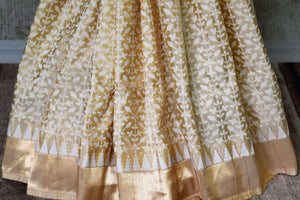 Captivating gold Benarasi silk saree with zari border buy online in USA and white floral design. Adorn your style with a range of exquisite handloom sarees from Pure Elegance Indian clothing store in USA. We have an exquisite range of Indian designer sarees, silk sarees, Banarasi saris and many other varieties also available at our online store.-pleats