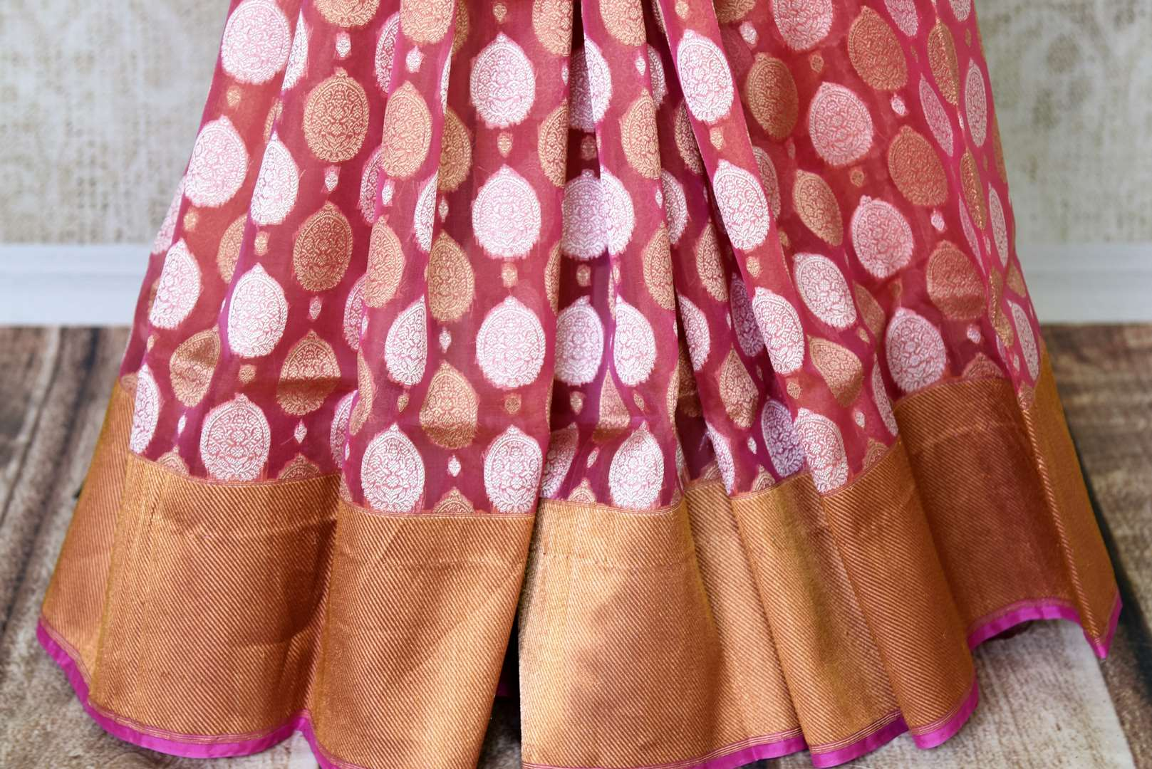 Flaunt your gorgeous self in this pink authentic banarsi silk saree. It comes with a beautiful dull gold border to exude the elegance of this sophisticated sari. Style it with a plain silk pink blouse and shop handcrafted silk sarees, designer linen saris, banarsi silk saree online or visit Pure Elegance store, USA. -pleats