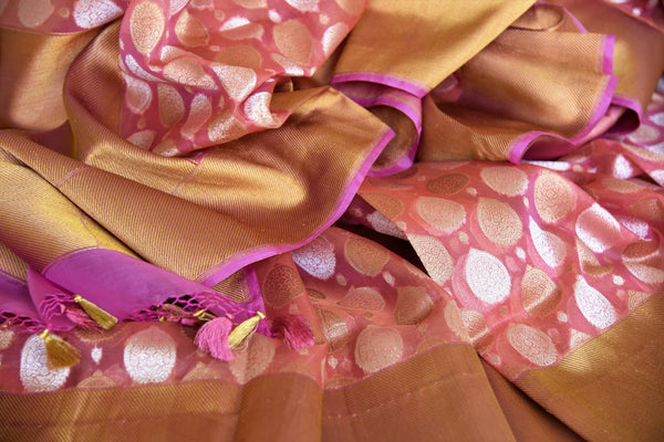 Flaunt your gorgeous self in this pink authentic banarsi silk saree. It comes with a beautiful dull gold border to exude the elegance of this sophisticated sari. Style it with a plain silk pink blouse and shop handcrafted silk sarees, designer linen saris, banarsi silk saree online or visit Pure Elegance store, USA. -details