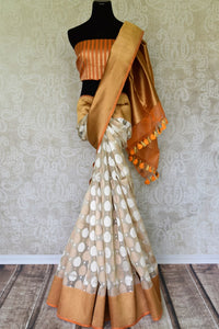 Leave them breathless as you step the aisle in this rich authentic white banarsi silk weave saree with a stunning gold zari border. The beautiful buta work adorned all-over the saree complemented with a contrasting gold woven blouse. Shop designer silk saree, ikkat sari online or visit Pure Elegance store, USA. -full view