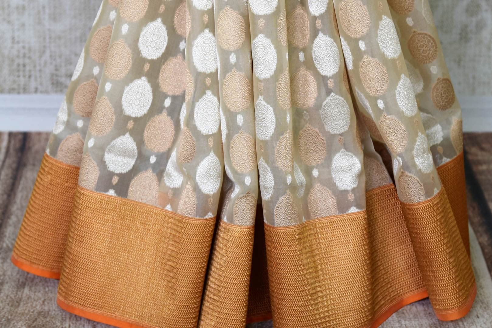 Leave them breathless as you step the aisle in this rich authentic white banarsi silk weave saree with a stunning gold zari border. The beautiful buta work adorned all-over the saree complemented with a contrasting gold woven blouse. Shop designer silk saree, ikkat sari online or visit Pure Elegance store, USA. -pleats