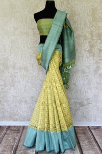 Serenade in solace in our yellow kora banarsi silk saree. The rustic blue border graces the wonderful facade of this silk sari, Style this stunning sari with a contrasting mint blue blouse with buta work. Shop handloom sarees, linen sari, chiffon sarees online or visit Pure Elegance store, USA.-full view