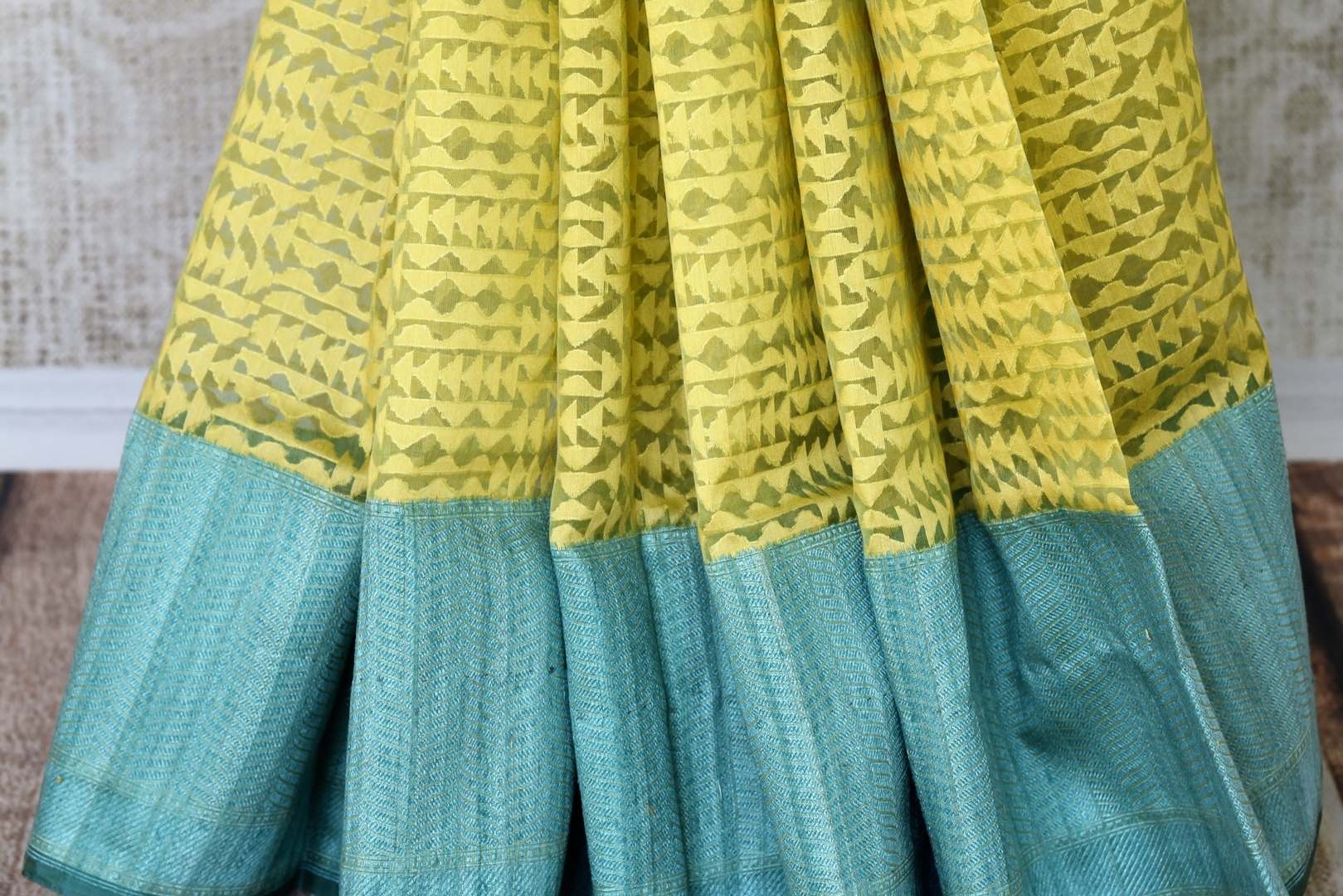 Serenade in solace in our yellow kora banarsi silk saree. The rustic blue border graces the wonderful facade of this silk sari, Style this stunning sari with a contrasting mint blue blouse with buta work. Shop handloom sarees, linen sari, chiffon sarees online or visit Pure Elegance store, USA.-pleats
