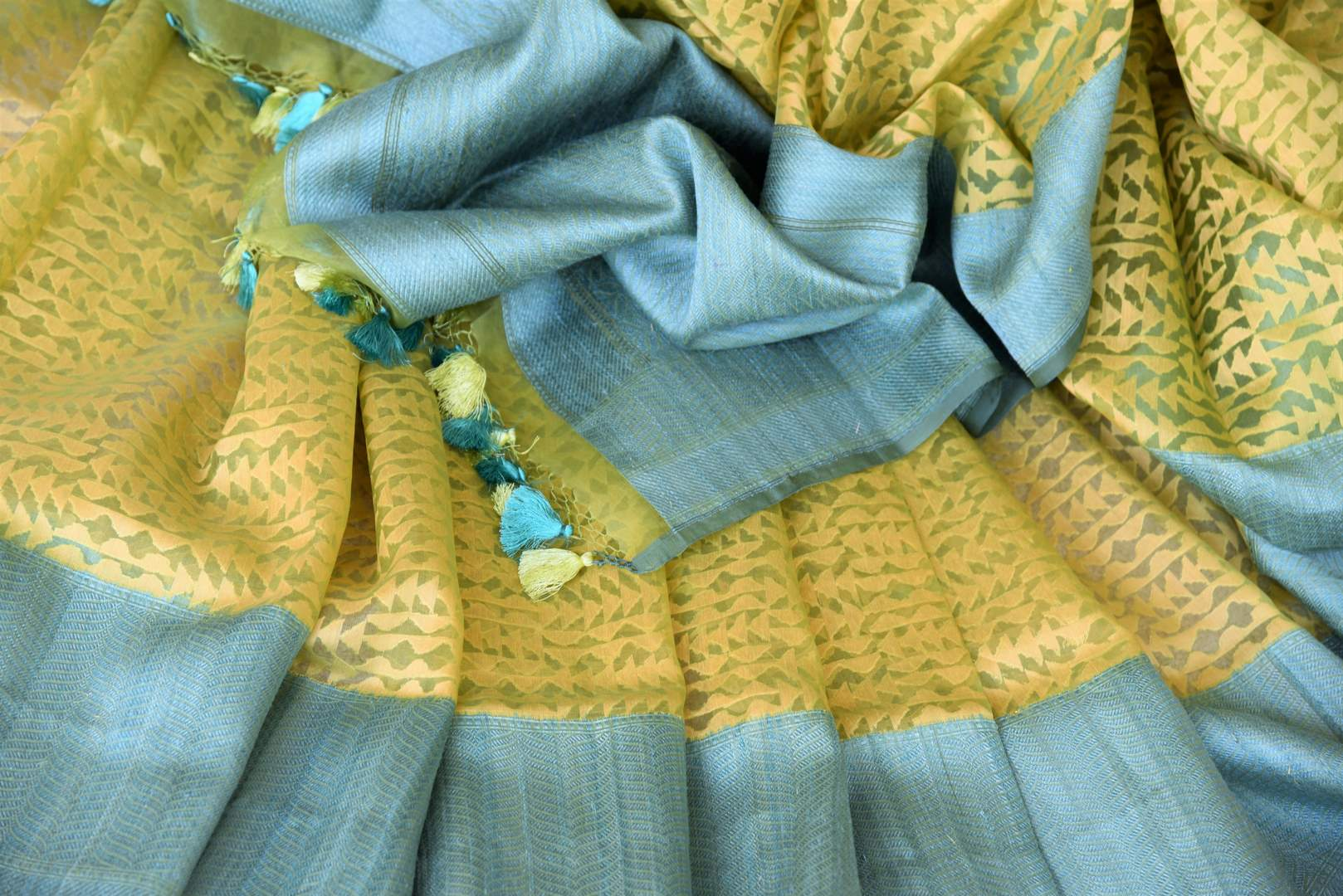 Serenade in solace in our yellow kora banarsi silk saree. The rustic blue border graces the wonderful facade of this silk sari, Style this stunning sari with a contrasting mint blue blouse with buta work. Shop handloom sarees, linen sari, chiffon sarees online or visit Pure Elegance store, USA.-details