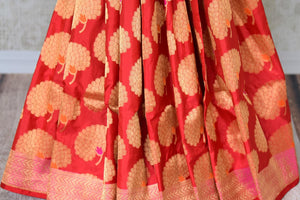 Shop red Banarasi silk saree with marigold flower buta online in USA. You can find a fine collection of Indian designer sarees in USA at Pure Elegance clothing store. Our range of traditional Indian clothing, silk sarees, wedding sarees,  at our online store is sure to leave you awestruck. -pleats
