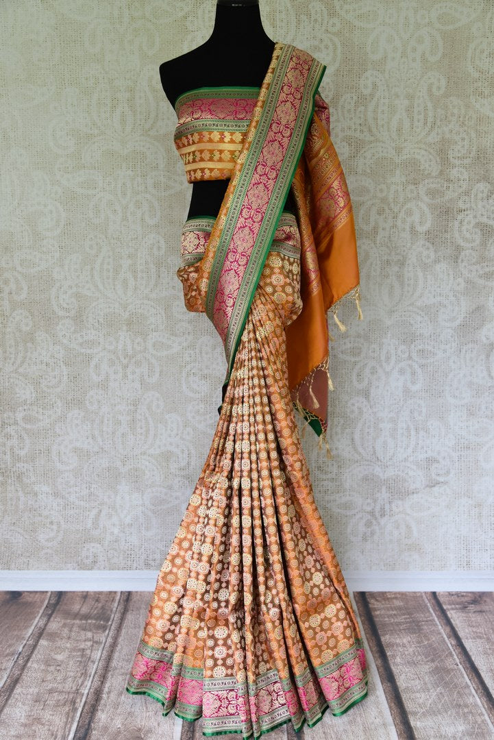 The ostentatious yet rich orange banarsi silk sari is a perfect pick for social events, parties etc. Style it with a stunning orange designer blouse. It features rich buta work all-over the drape. Shop designer silk sari, chiffon saree, embroidered sari online or visit Pure Elegance store, USA. -full view