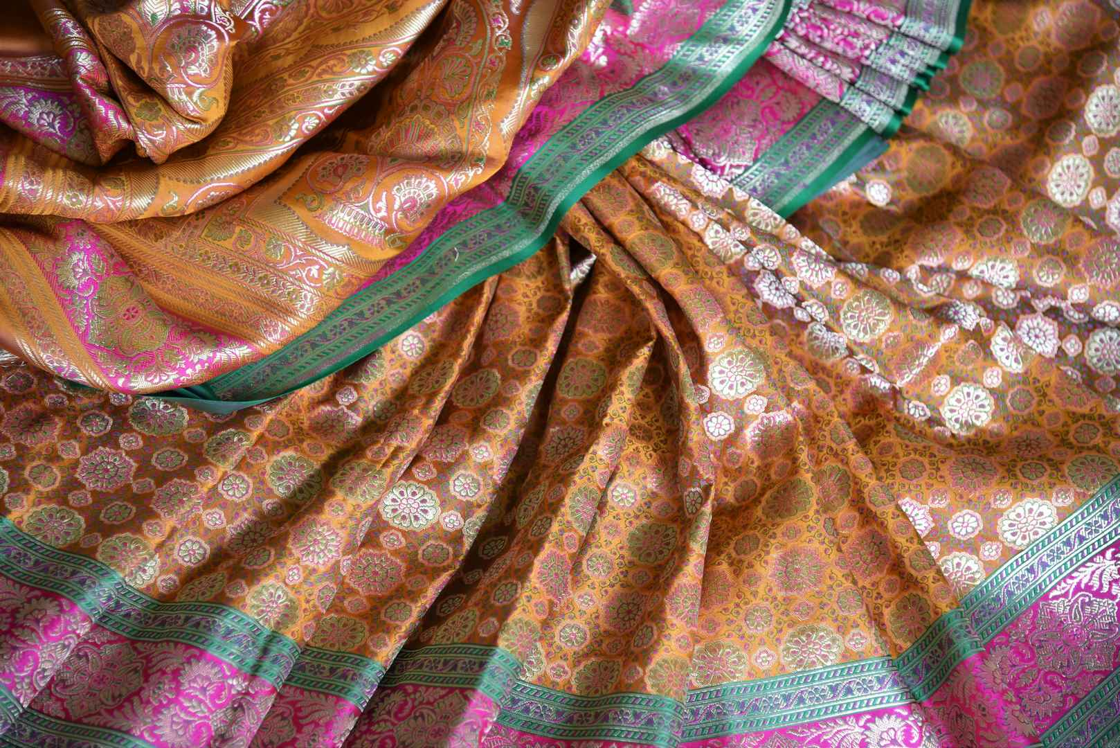The ostentatious yet rich orange banarsi silk sari is a perfect pick for social events, parties etc. Style it with a stunning orange designer blouse. It features rich buta work all-over the drape. Shop designer silk sari, chiffon saree, embroidered sari online or visit Pure Elegance store, USA. -details