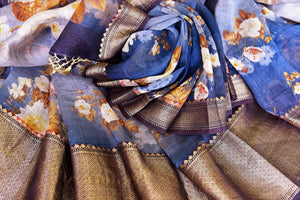 Emanate elegance in this blue chanderi silk organza sari. It features floral printed work which comes with a brown zari banarsi silk border. Style it with a designer blue floral printed blouse with a gold border. Shop such banarsi silk saris, embroidered sarees, kalamkari sari online or visit Pure Elegance store, USA.-details