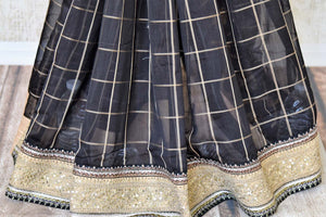 Buy black check linen saree with saree blouse online in USA and embroidered border. Add tasteful Indian woven saris to your ethnic wardrobe from Pure Elegance Indian fashion store in USA. We have an exclusive range of Indian designer sarees, wedding saris, handloom sarees to make your Indian look absolutely captivating.-pleats