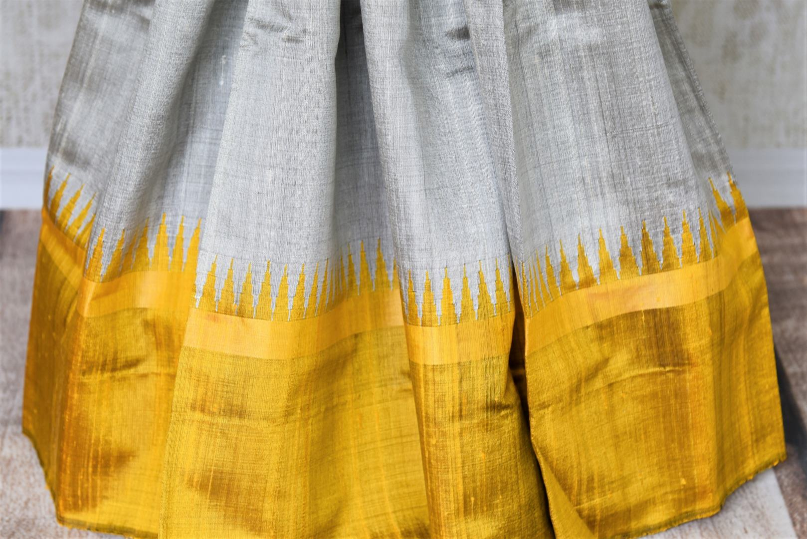 Buy grey tussar dupion silk sari online in USA with mustard yellow border. Add grace to your ethnic look with Indian designer silk sarees available at Pure Elegance Indian clothing store for women in USA or shop online.-pleats