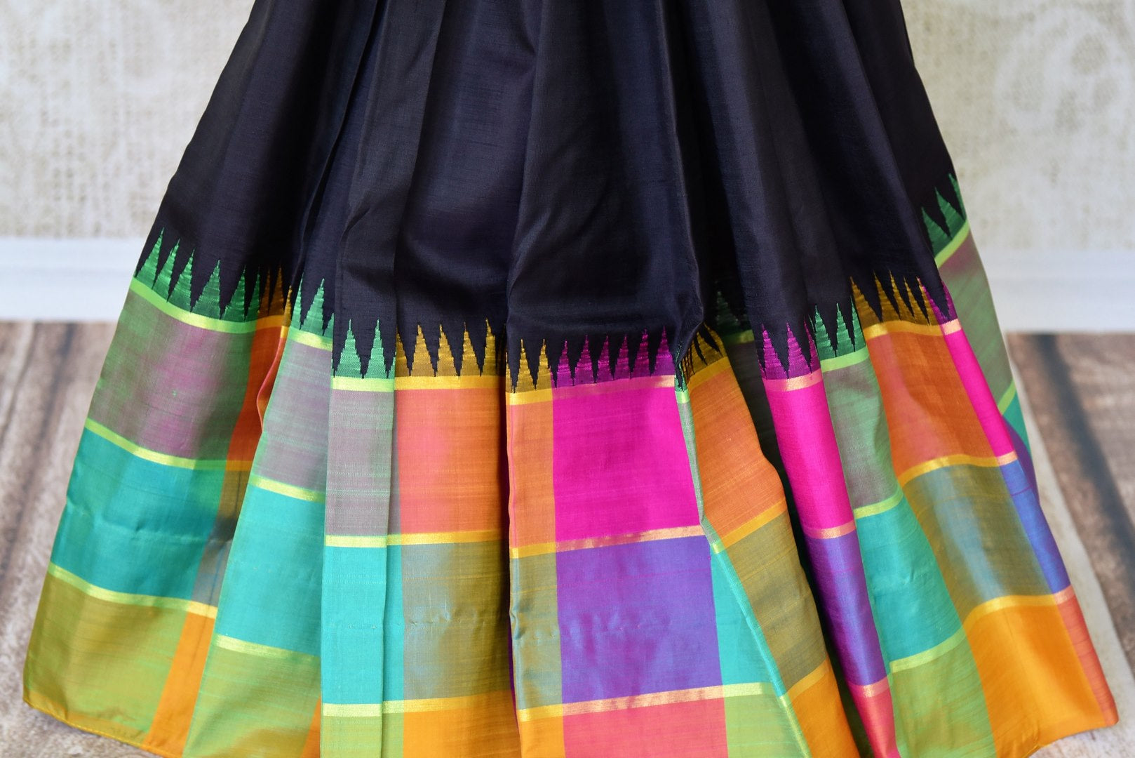 Buy online black Kanchipuram silk saree in USA with multicolor check border.  For all the Indian women in USA who love Indian clothing and sarees, Pure Elegance clothing store in USA brings an exquisite collection of designer silk sarees, Kanjivaram silk saris online and in store. Shop now.-pleats