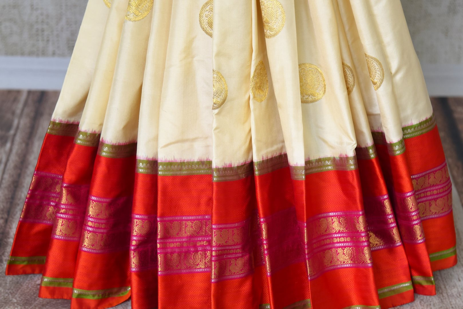 Buy off white kanji ikkat saree online in USA with red zari border and zari buta. Add the richness of Indian culture to your saree look with Kanjeevaram silk saris, Indian designer saris, bridal sarees from Pure Elegance Indian clothing in USA or shop online.-pleats
