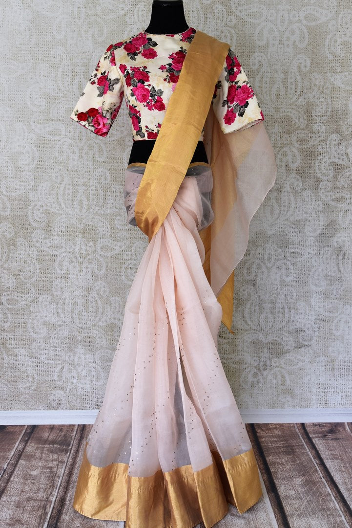 Shop powder pink organza silk sari with bright zari border online in USA. It comes with a beautiful floral print satin sari blouse to complete your sari look. Take your Indian style a notch up with a range of beautiful Indian clothing from Pure Elegance. We have a range of traditional Indian sarees, designer sarees in USA online and our fashion store.-full view
