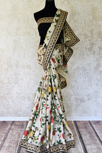 Buy off-white floral print muga tussar saree online in USA with embroidered border. Take your Indian style a notch up with a range of beautiful Indian clothing from Pure Elegance fashion store. We have a range of traditional Indian saris, designer sarees, handloom sarees in USA online and in our store. Shop now.-full view