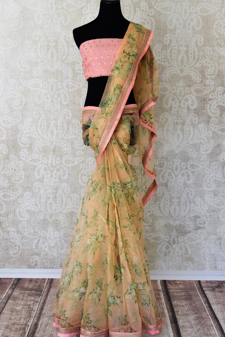 Buy peach floral organza saree online in USA with pink embroidered border. Take your Indian style a notch up with a range of beautiful Indian clothing from Pure Elegance fashion store. We have a range of traditional Indian sarees, designer sarees, handloom sarees in USA online and in our store. Shop now.-full view