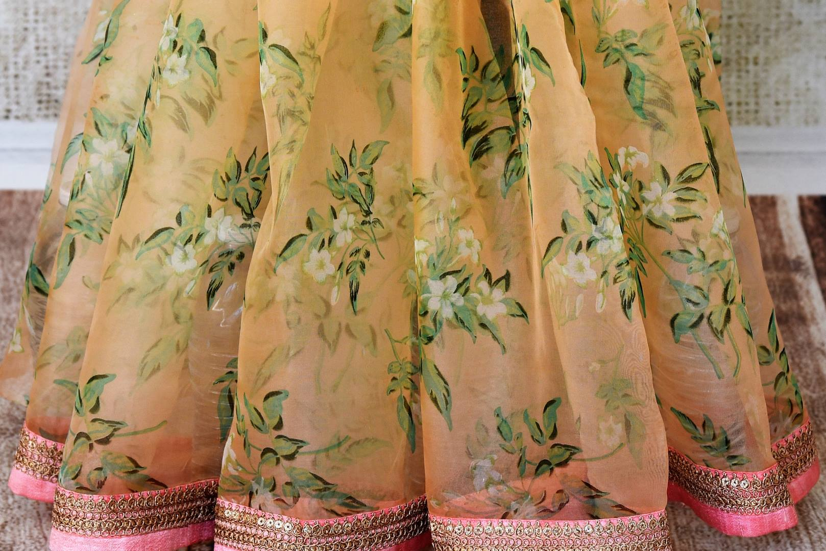 Buy peach floral organza saree online in USA with pink embroidered border. Take your Indian style a notch up with a range of beautiful Indian clothing from Pure Elegance fashion store. We have a range of traditional Indian sarees, designer sarees, handloom sarees in USA online and in our store. Shop now.-pleats