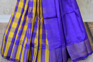 Shop blue and yellow half check and half plain Kanjivaram silk saree online in USA. Adorn your style with a range of exquisite Kanchipuram silk saris from Pure Elegance clothing store in USA. We have an exquisite range of Indian designer sarees, silk sarees, Banarasi saris and many other varieties also available at our online store.-pleats