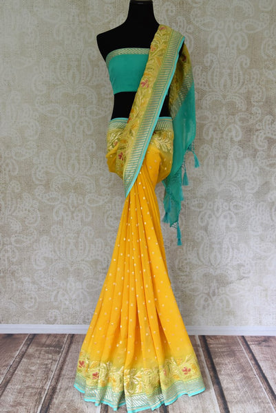 Shop yellow Banarasi georgette saree online in USA with floral zari border from Pure Elegance online store. Visit our exclusive Indian fashion store in USA and get floored by a range of exquisite pure handloom sarees, Banarasi sarees, silk sarees, Indian jewelry and much more to complete your ethnic look.-full view