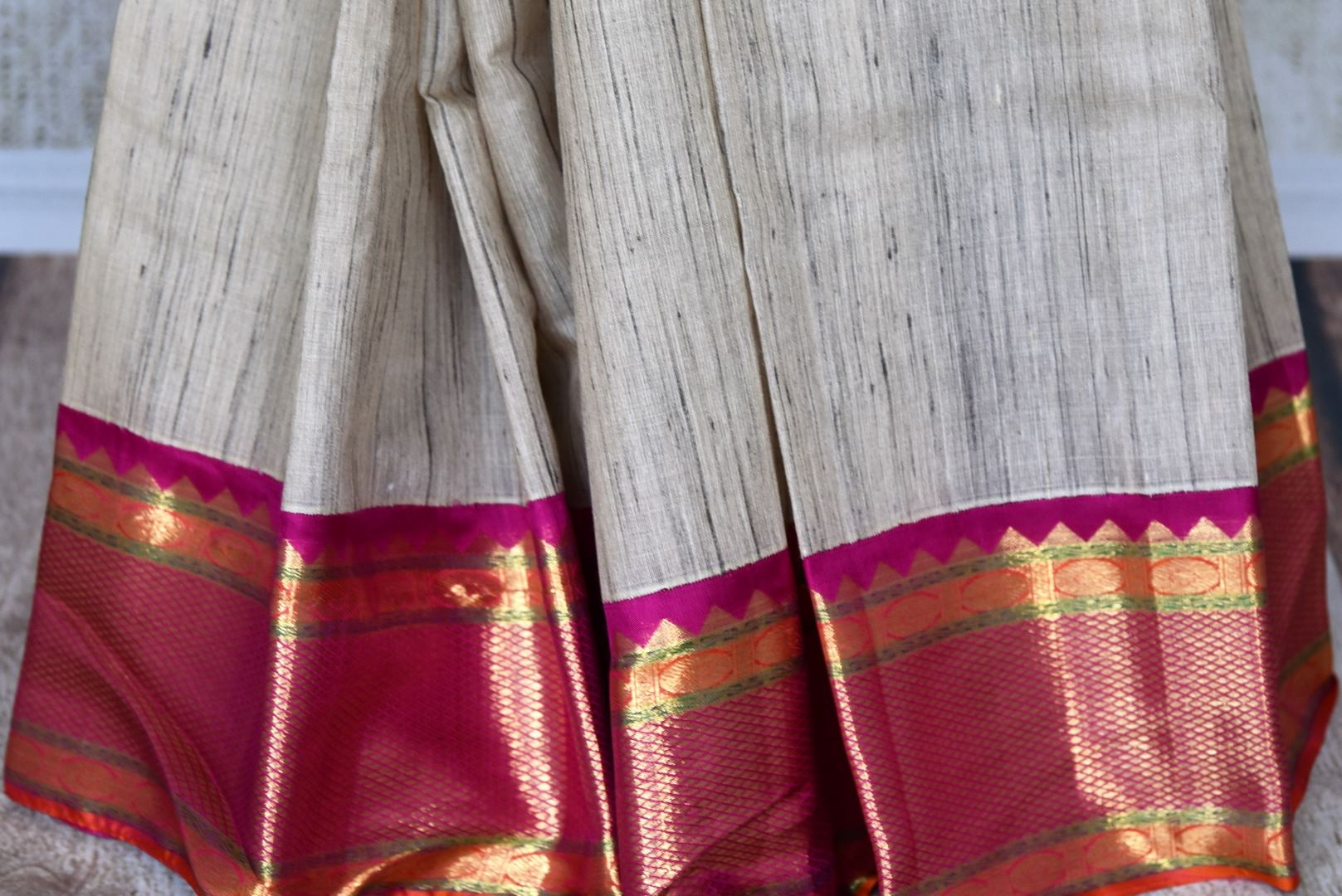 Buy off-white Kanjivaram sari with multicolor zari border online in USA from Pure Elegance. Be an epitome of Indian fashion on special occasions with beautiful designer sarees, Banarasi sarees, Kanchipuram silk sarees available at our Indian fashion store in USA. -pleats