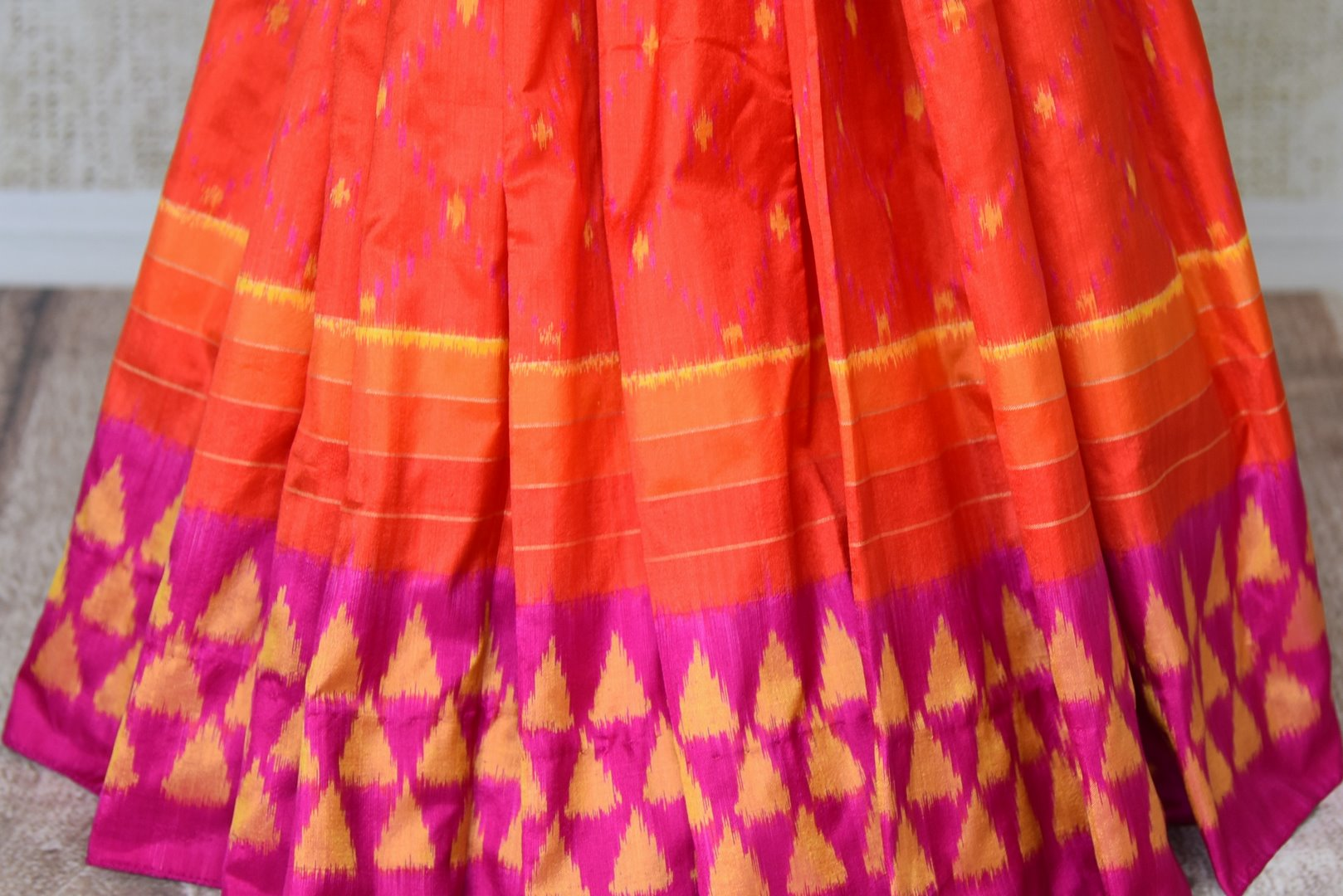 Shop traditional red ikkat silk sari online in USA with pink ikat border. Find a splendid collection of Indian designer sarees with blouses in USA at Pure Elegance Indian clothing store. Make a striking appearance on festive occasions by shopping from a range of pure silk saris, Banarasi sarees, embroidered saris from our online store.-pleats