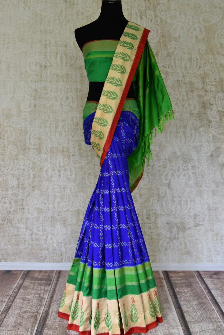 Shop ethnic blue color ikkat silk sari online in USA with green ikat border. Find a splendid collection of Indian designer sarees with blouses in USA at Pure Elegance Indian clothing store. Make a striking appearance on festive occasions by shopping from a range of pure silk saris, Banarasi sarees, embroidered saris from our online store.-full view