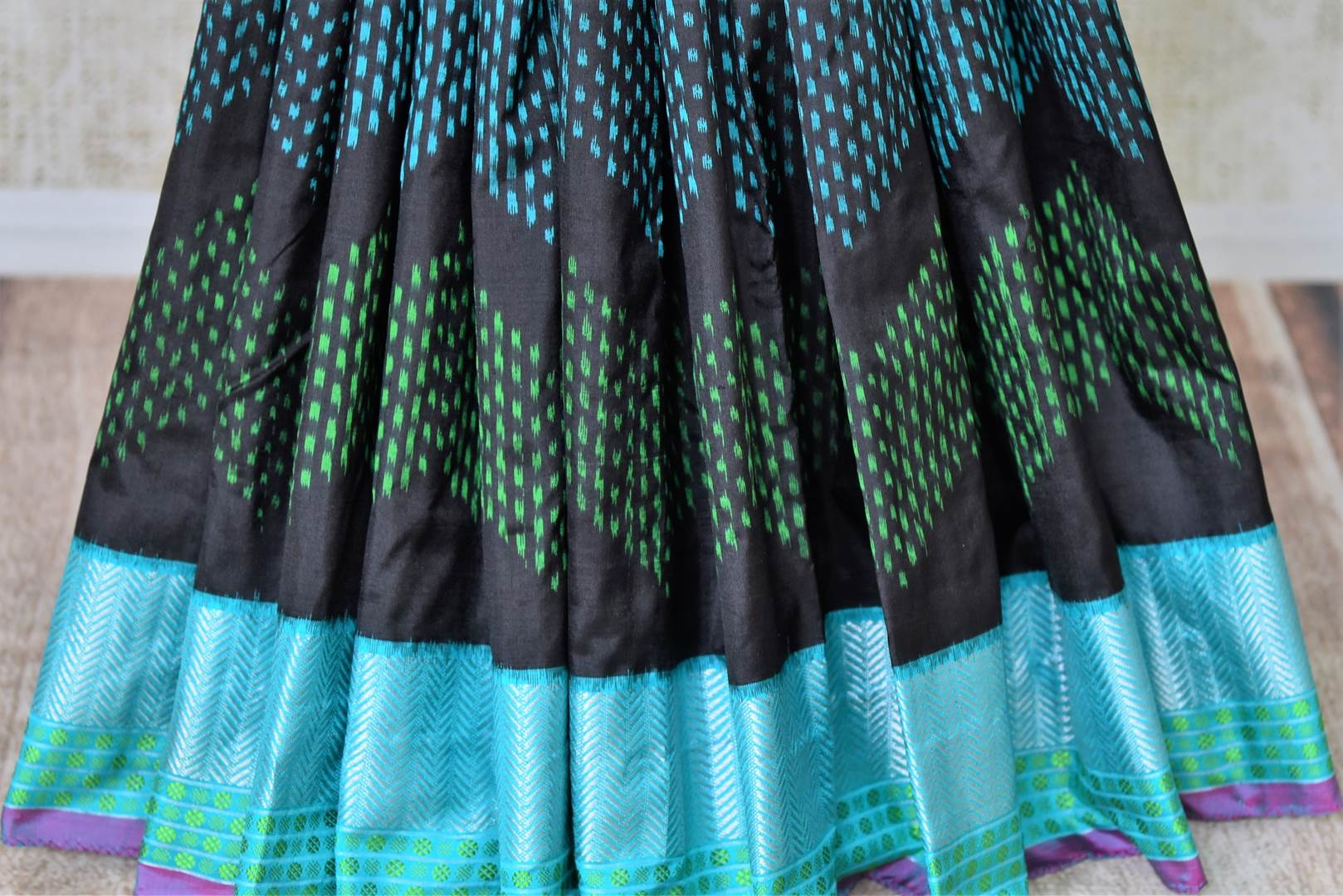 Shop elegant black ikat silk sari with blue zari border online in USA from Pure Elegance. Be occasion ready always with a range of beautiful designer saris, pure silk sarees, handloom saris, Kanchipuram sarees available at our Indian fashion store in USA. Grab your favorite pieces now also available at our online store.-pleat