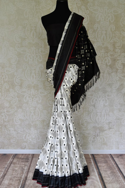 Buy white double ikat silk sari online in USA with black border. Find a splendid collection of Indian designer sarees with blouses in USA at Pure Elegance Indian clothing store. Make a striking appearance on festive occasions by shopping from a range of pure silk saris, Banarasi sarees, embroidered saris from our online store.-full view