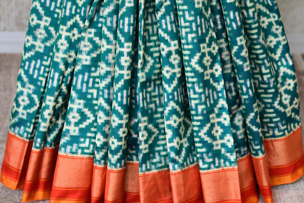 Buy green double ikat silk saree online in USA with red border. Find a splendid collection of Indian designer sarees with blouses in USA at Pure Elegance Indian clothing store. Make a striking appearance on festive occasions by shopping from a range of pure silk saris, Banarasi sarees, embroidered saris from our online store.-pleats