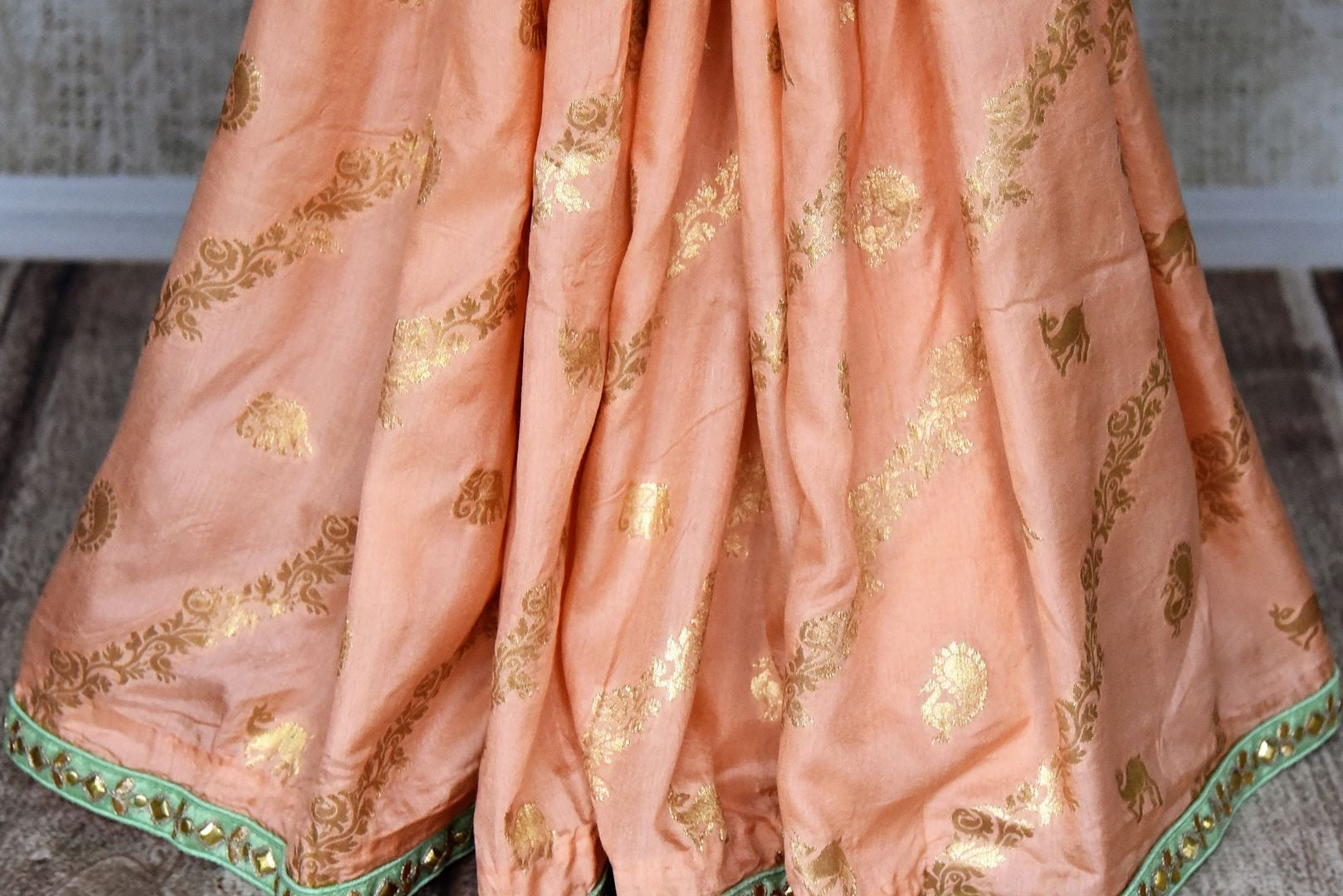 Shop peach tussar georgette saree online in USA with gota work border and saree blouse. Be the talk of every occasion in beautiful Indian designer saris, pure silk sarees, Banarasi sarees from Pure Elegance clothing fashion store in USA this wedding season.-pleats