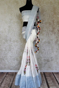 Buy white embroidered linen saree online in USA with blue check border. Shine bright on special occasions with traditional Indian sarees, handloom sarees, pure silk sarees in rich colors and designs from Pure Elegance Indian fashion store in USA.-full view