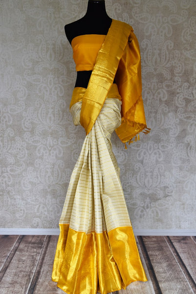 Buy off-white zari stripes Kanjeevaram saree with yellow zari border online in USA from Pure Elegance. Make your ethnic style perfect with a range of exquisite Indian designer saris with blouses, embroidered sarees, Kanjivaram silk saris available at our exclusive Indian fashion store in USA and also on our online store. Shop now.-full view