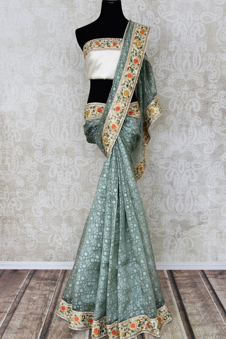 Shop grey printed organza saree online in USA with embroidered border. Pick your favorite Indian sarees from a colorful collection available at Pure Elegance Indian fashion store in USA. We have an alluring range of handwoven sarees, pure silk sarees, traditional Banarasi sarees for every occasion.-full view