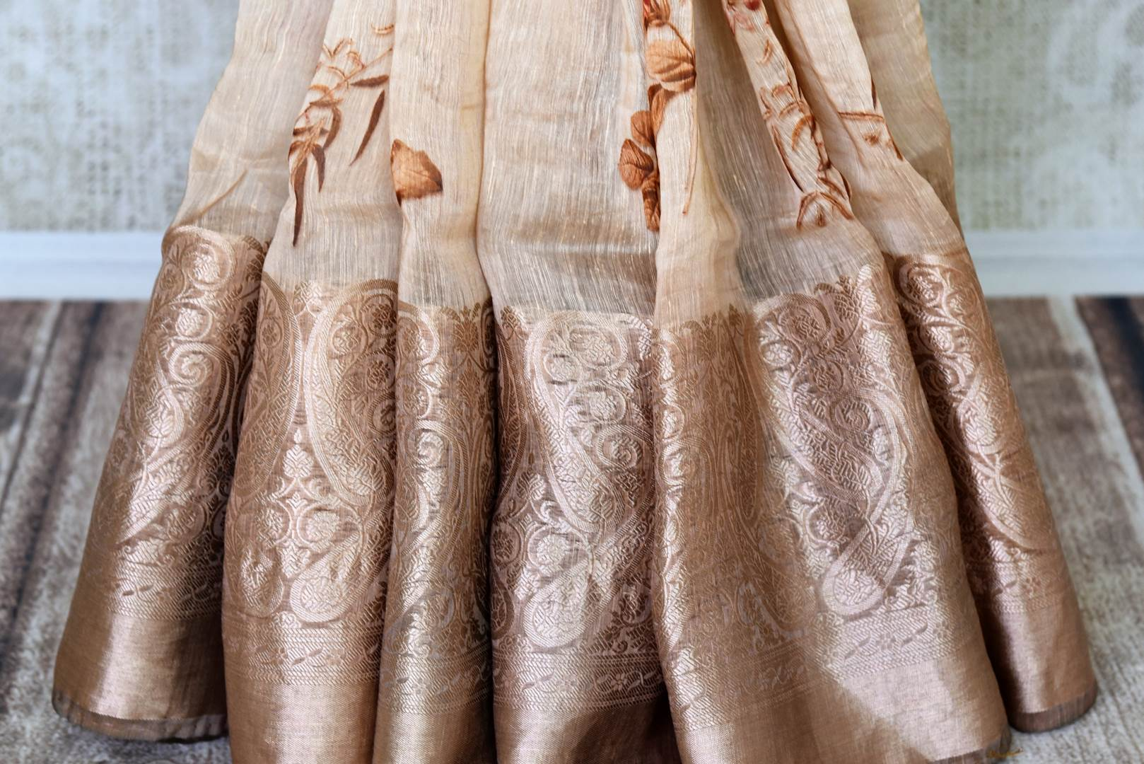 Buy cream floral print linen Benarasi saree online in USA with golden border. Update your saree wardrobe with stunning Indian handwoven sarees from Pure Elegance Indian fashion store in USA. Shop now.-pleats