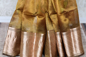 Buy golden tissue linen copper border Banarasi saree online in USA with floral print. Enhance your ethnic style with exquisite Indian handloom saris from Pure Elegance Indian clothing store in USA. Pick from a range of vibrant silk sarees, Banarasi sarees, Kanchipuram silk sarees for a stunning ethnic style.-pleats