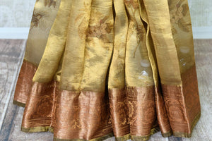 Shop stunning golden green floral tissue linen sari online in USA with golden border. Update your saree wardrobe with stunning Indian handwoven sarees from Pure Elegance Indian fashion store in USA. Shop now.-pleats